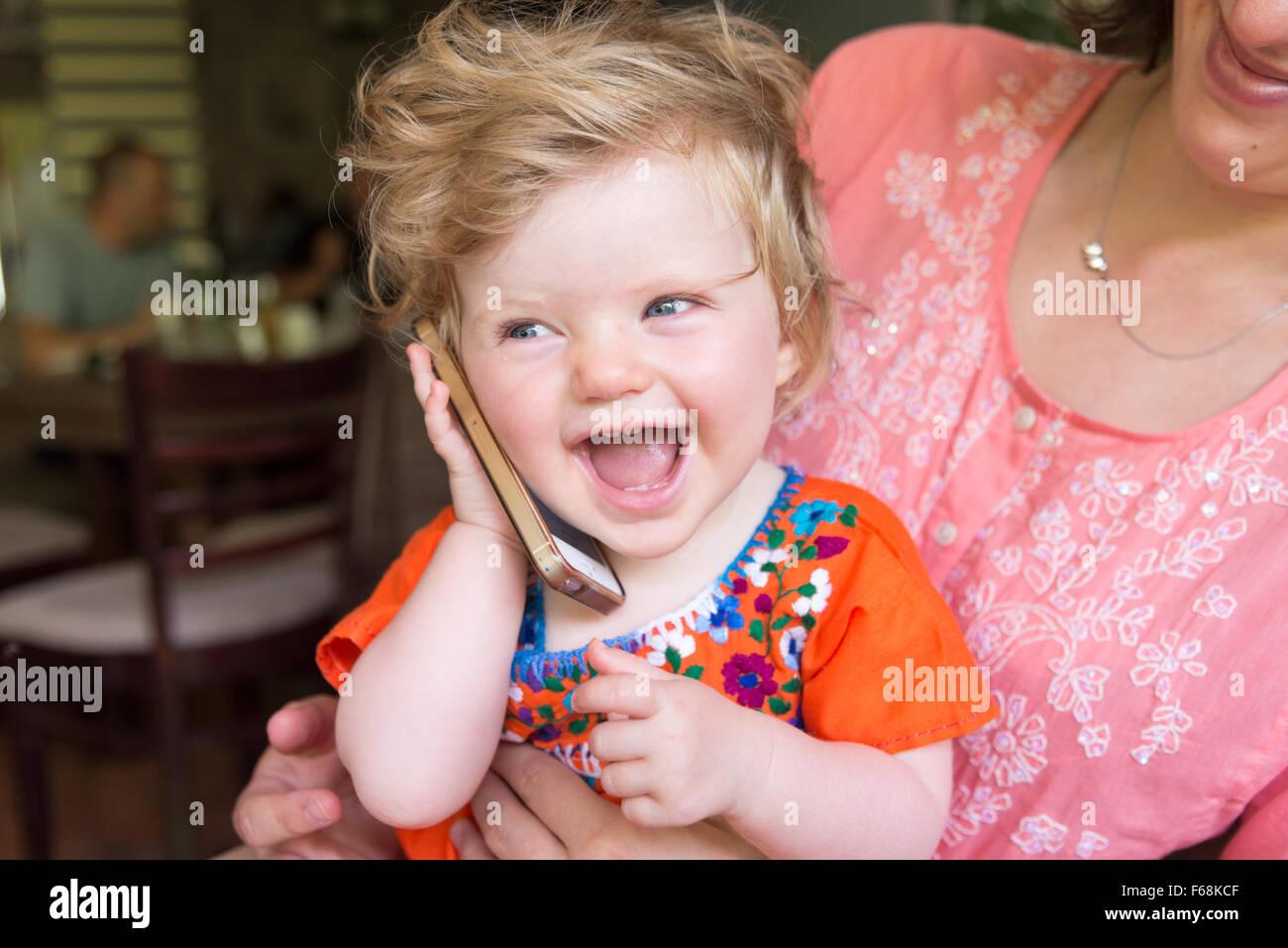 Un anno di età baby parlando su un Apple iPhone Immagini Stock