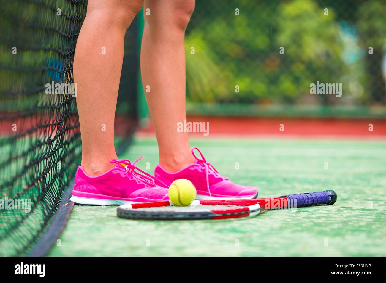 Primo piano della scarpe con la racchetta da tennis e la sfera all'aperto su corte Immagini Stock