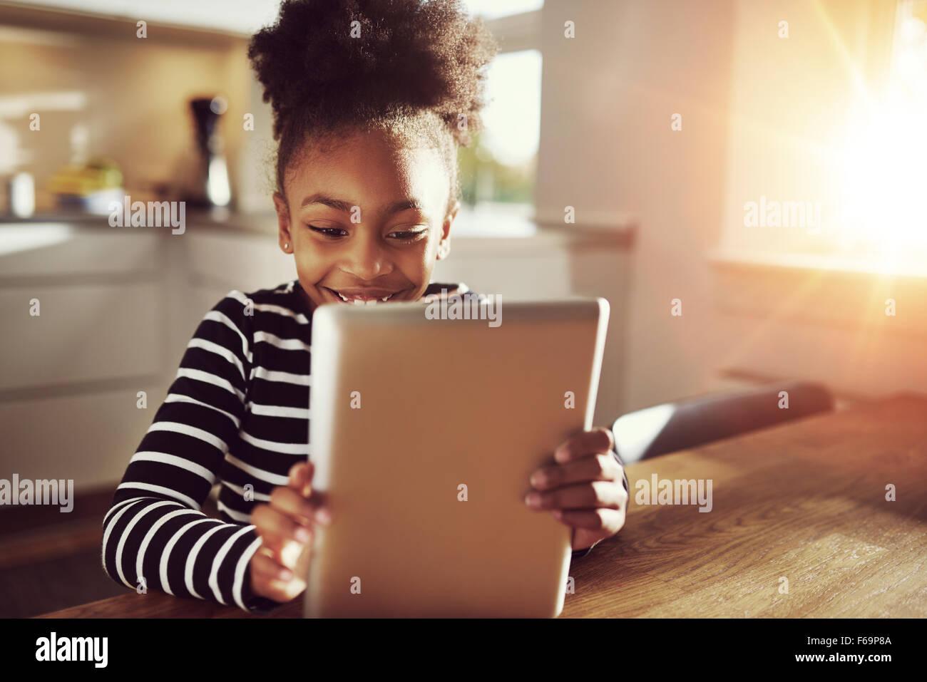 Piccolo felice di etnia nero ragazza seduti a casa in cucina la lettura su un computer tablet grinning con piacere, Immagini Stock