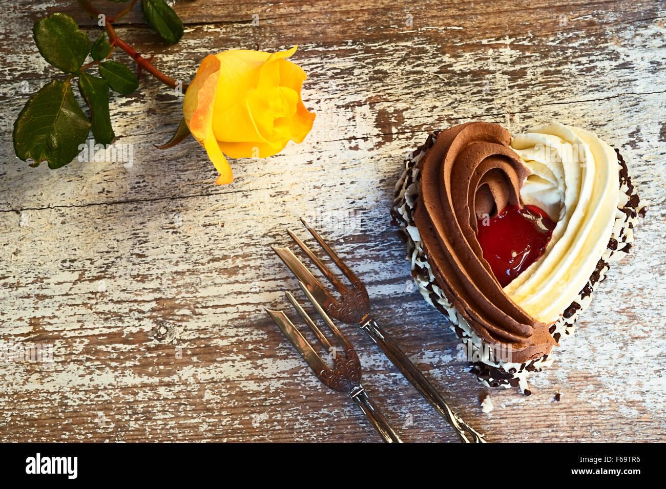 Still Life with a forma di cuore torta, due forcelle di pasticceria e una rosa gialla Immagini Stock