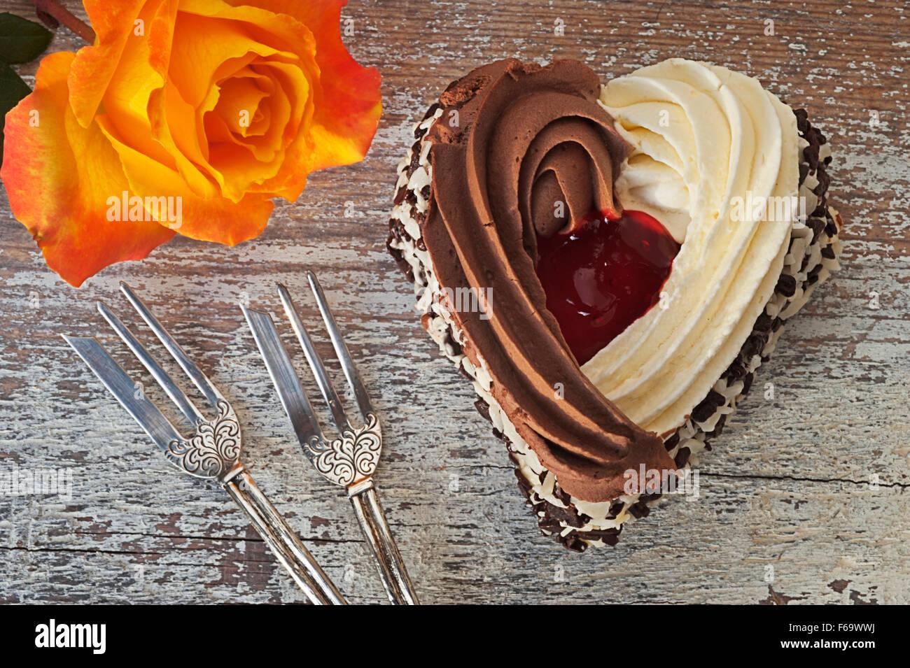 Still Life with a forma di cuore la torta, ornato di due forcelle di pasticceria e un arancione rosa Immagini Stock