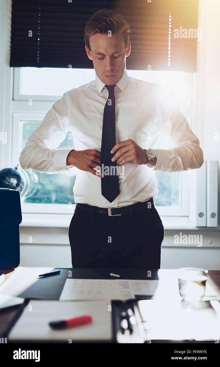 CEO executive business tipo maschio bianco la legatura la cravatta mentre permanente al desk presso il suo ufficio, Immagini Stock