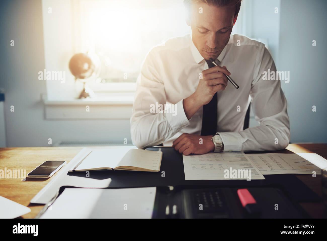 Commercio serio uomo che lavora su documenti cercando concentrata con valigetta e telefono cellulare sul tavolo Immagini Stock