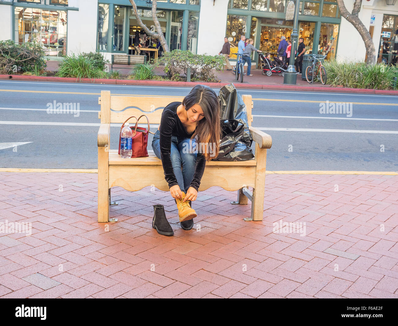 Un giovane adulto ispanica donna cambia in scarpe nuove che ha appena acquistato su una panchina pubblica sul marciapiede Foto Stock