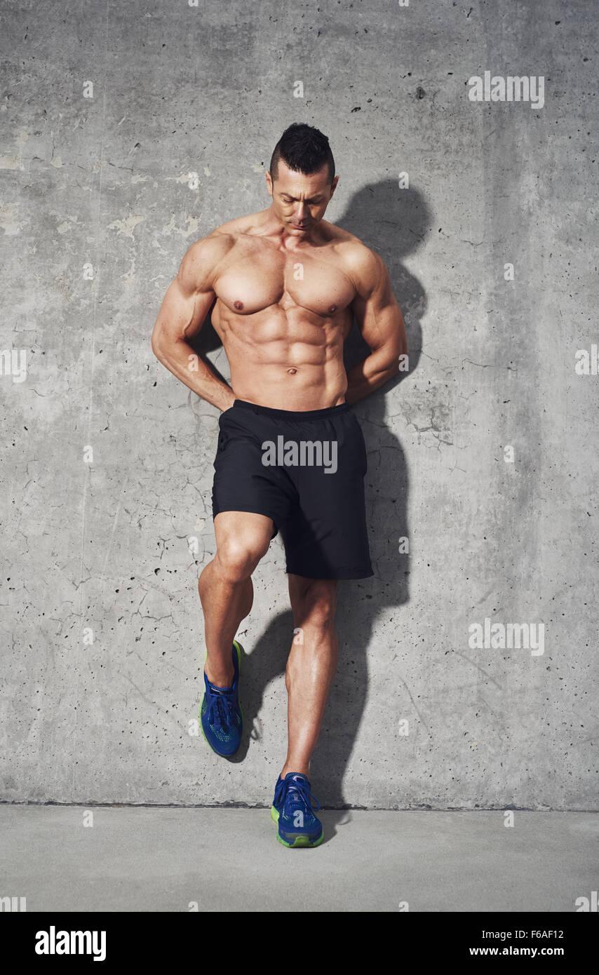Modello di fitness in piedi contro lo sfondo grigio, nessuna camicia che mostra i muscoli addominali, close up, Immagini Stock