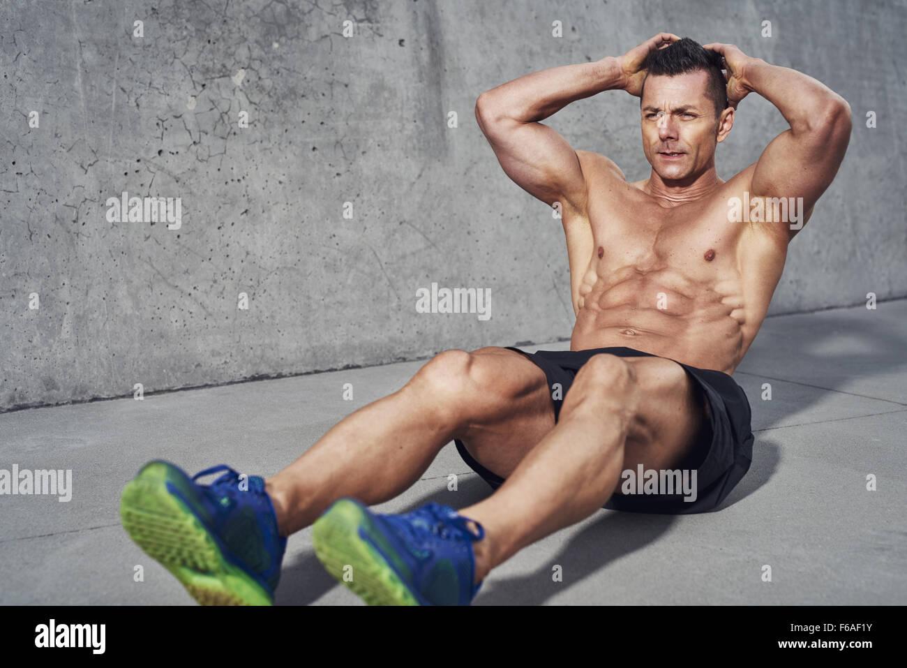 Maschio modello fitness facendo sit ups e sgranocchia allenamento dei muscoli addominali, six pack visibile e non Immagini Stock