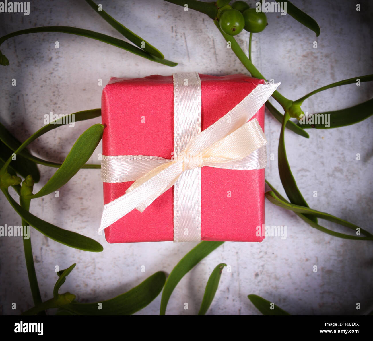 Rosso avvolto regalo per Natale o altra celebrazione e il ramo di vischio verde sul vecchio sfondo di legno Immagini Stock