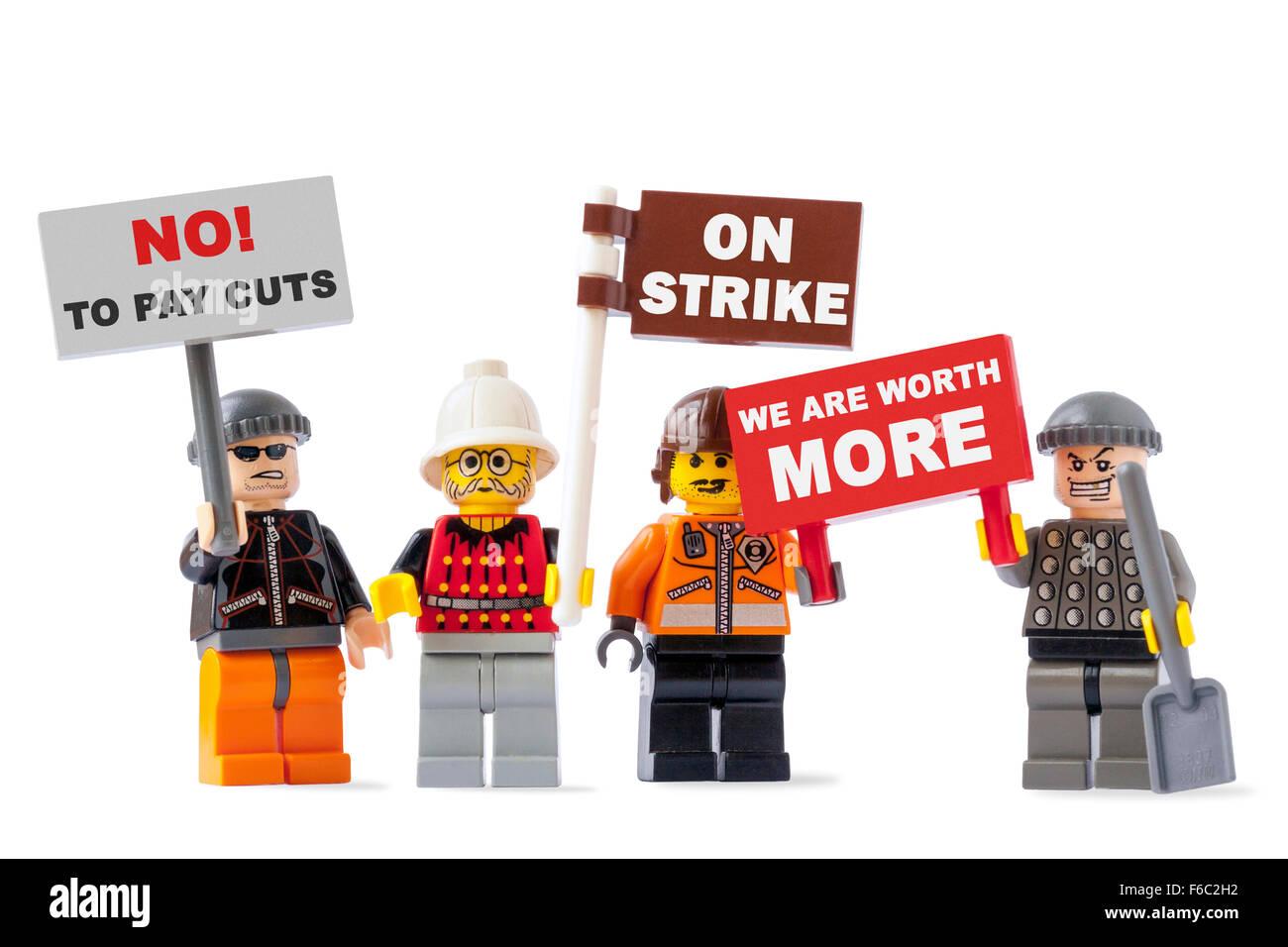 Lavoratori in sciopero concetto con quattro statuette giocattolo isolati su sfondo bianco e segni di contenimento Immagini Stock