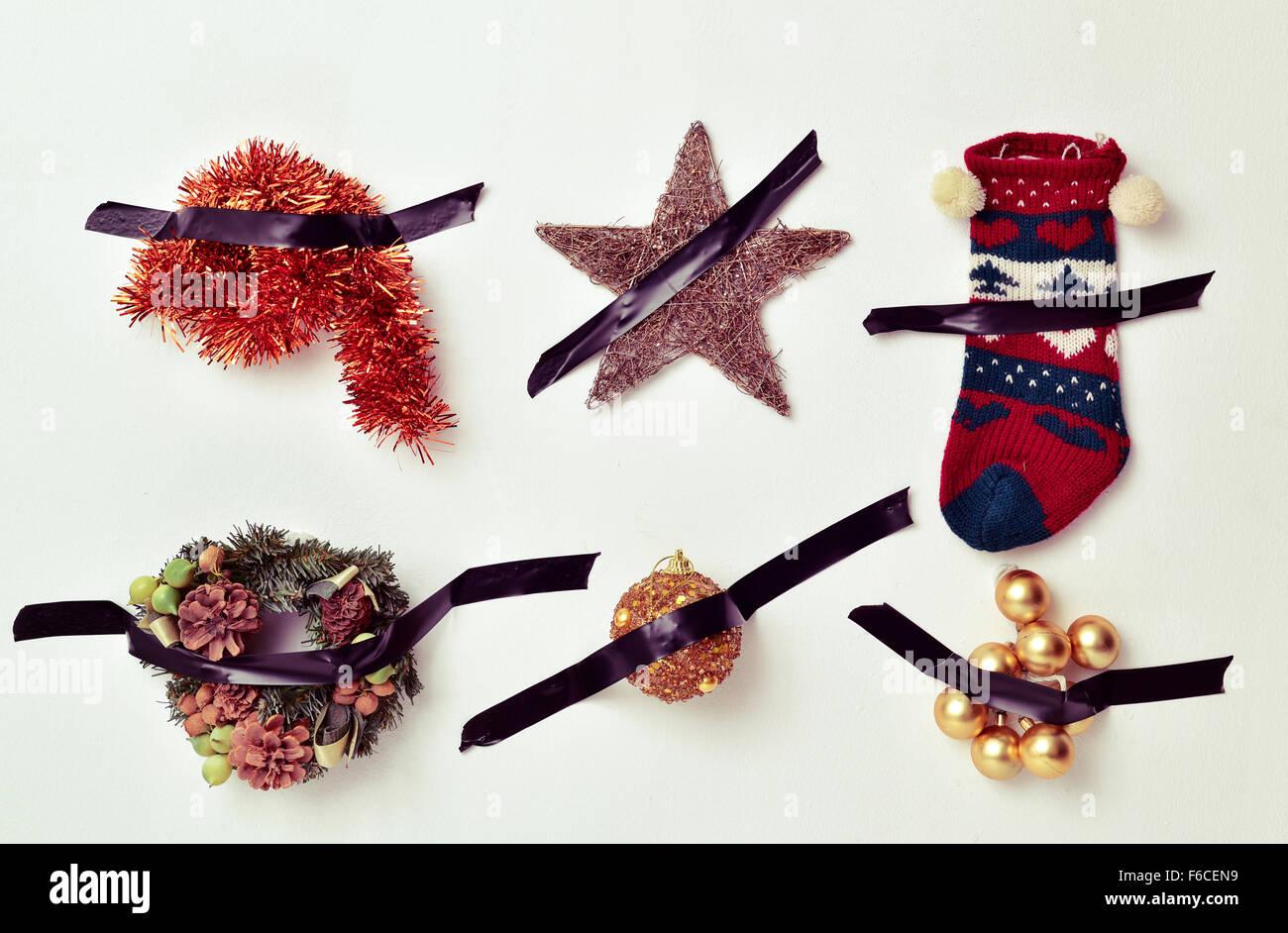 Alcune diverse decorazioni di Natale, come tinsel, una stella, una calza o baubles, attaccato ad una parete bianca Immagini Stock