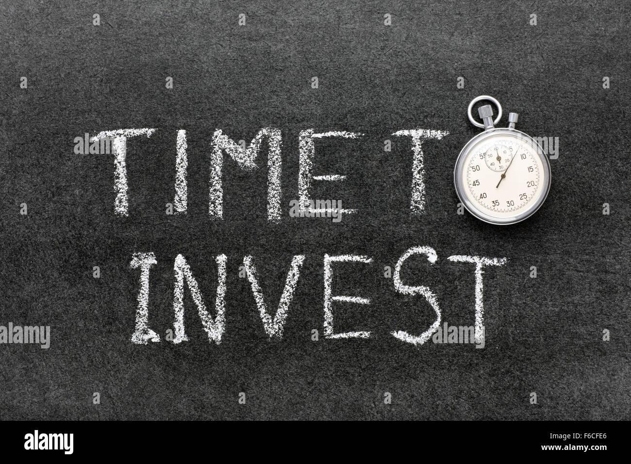 È tempo di investire una frase scritta a mano sulla lavagna con vintage cronometro preciso utilizzato al posto Immagini Stock