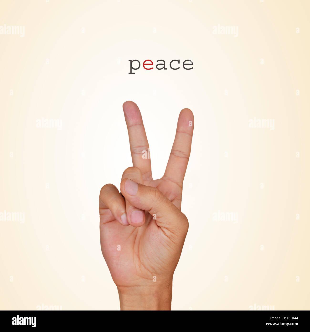 Primo piano della mano di un giovane uomo che dà il segno di V e la parola pace su uno sfondo beige Immagini Stock