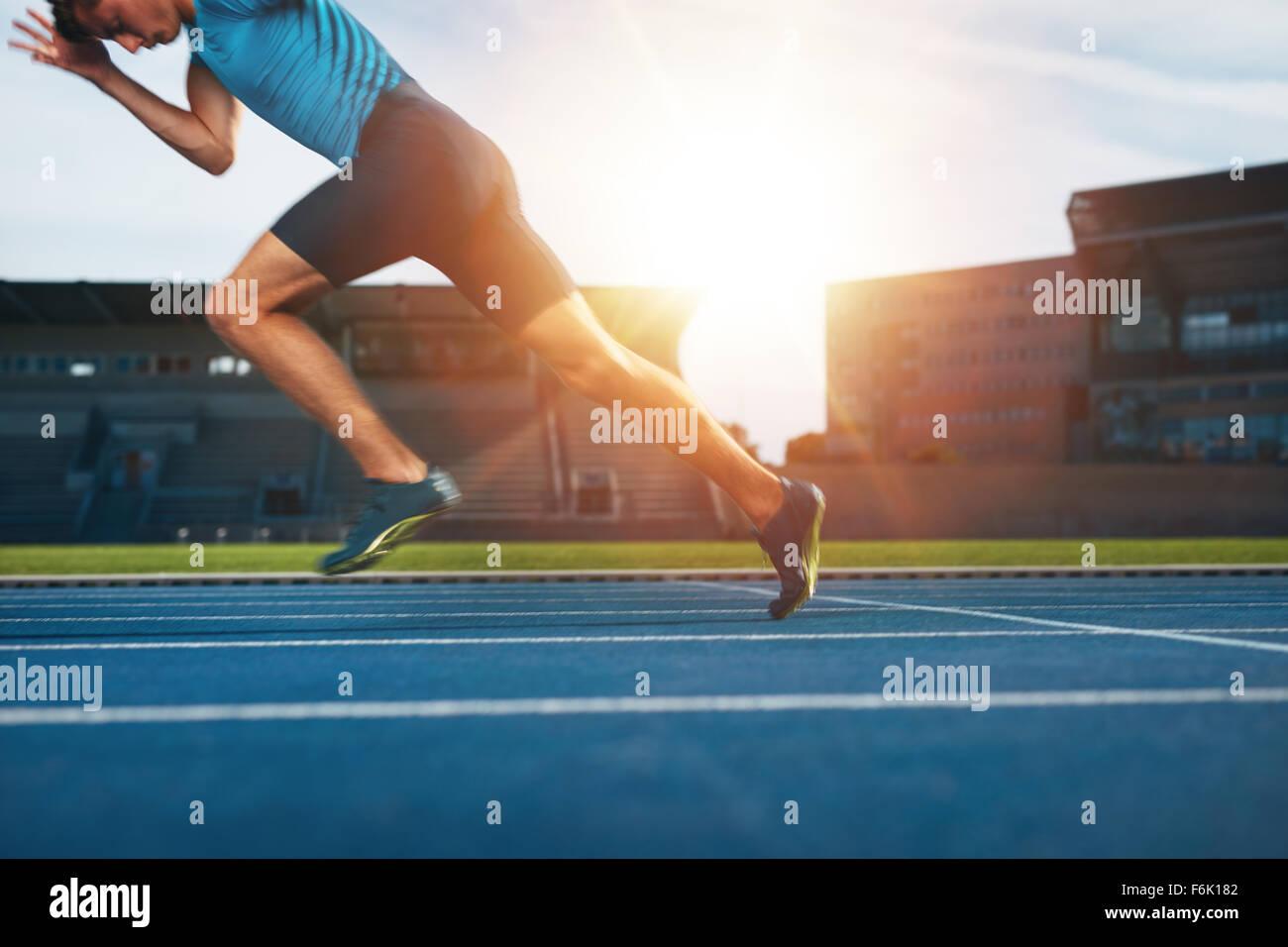 Colpo di giovane atleta maschio lanciando fuori dalla linea di partenza in una gara. Runner in esecuzione sulla Immagini Stock