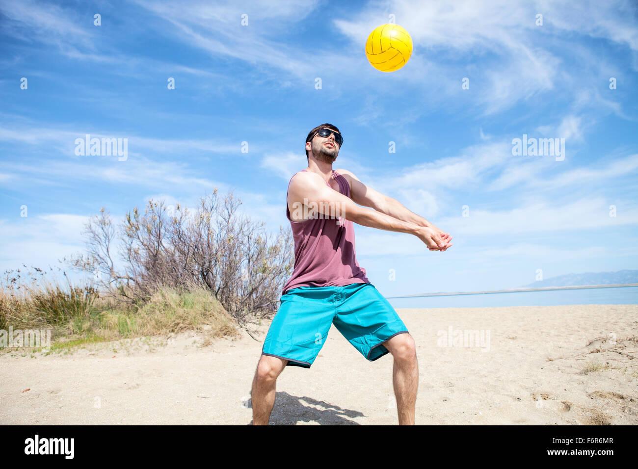 Giovane uomo a giocare a beach volley Immagini Stock