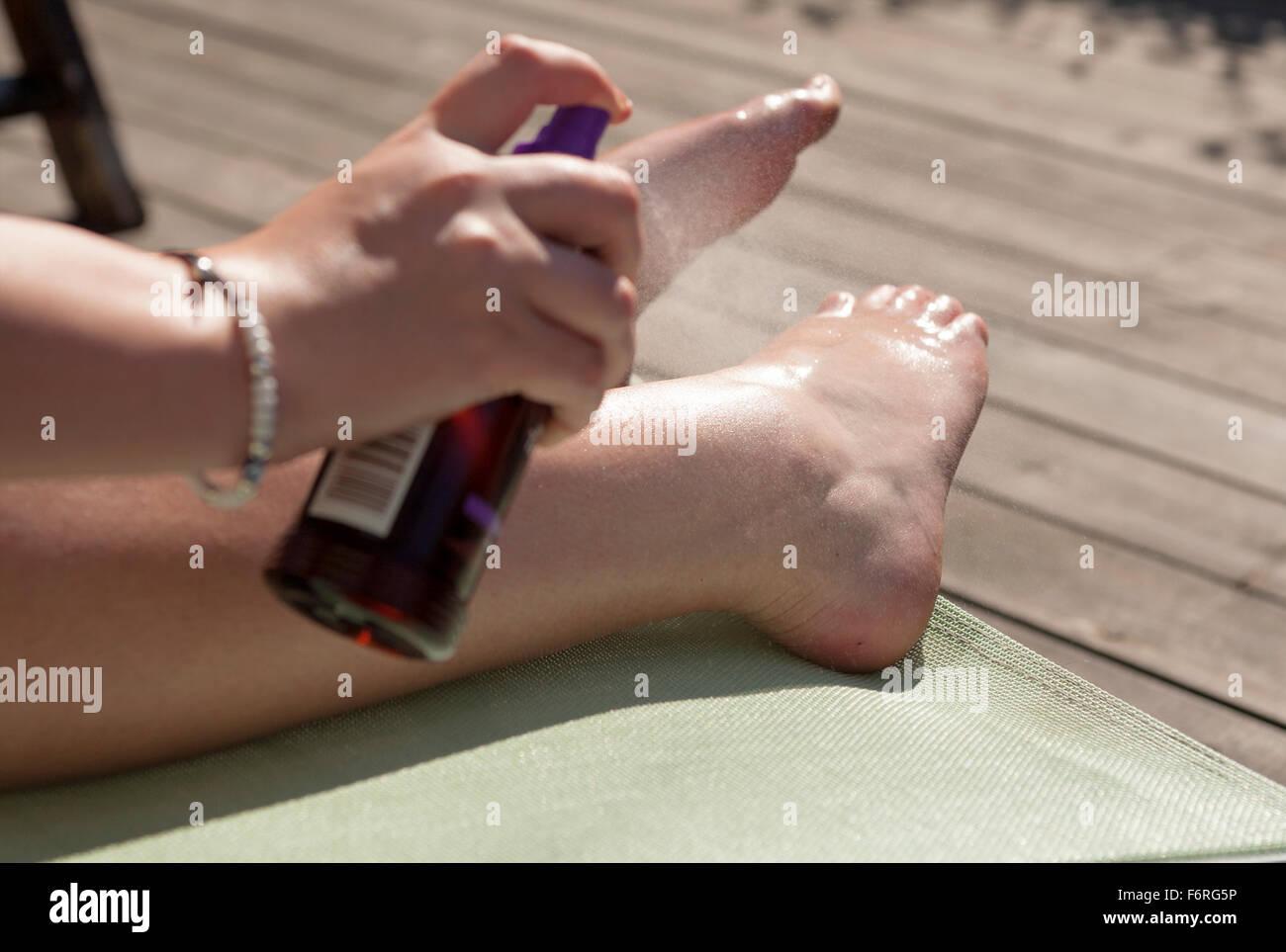 La donna sulla sedia a sdraio l'applicazione di crema di protezione solare spray per proteggere la sua pelle Immagini Stock