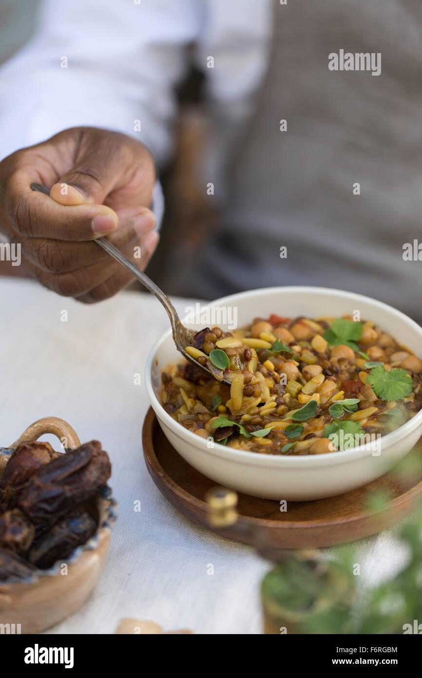 Un uomo è in procinto di mangiare una ciotola di hearthy harira. Immagini Stock
