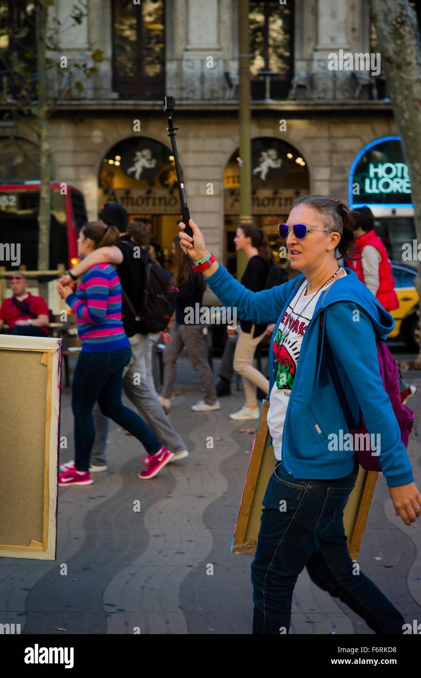 Una donna cammina attraverso Les Rambles di Barcellona tenendo una telecamera aloft su un bastone selfie. Immagini Stock
