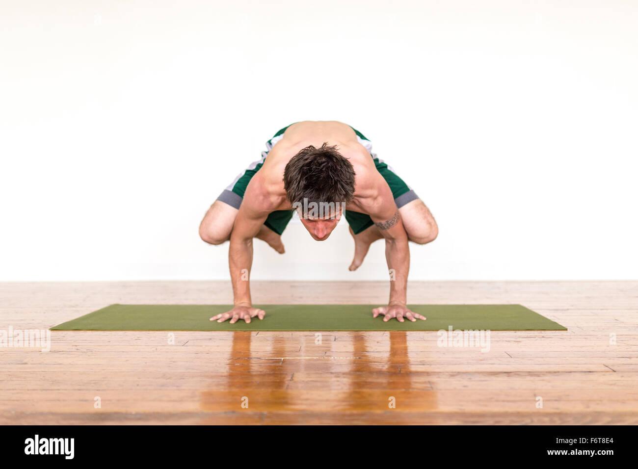 Uomo a praticare yoga in studio Immagini Stock