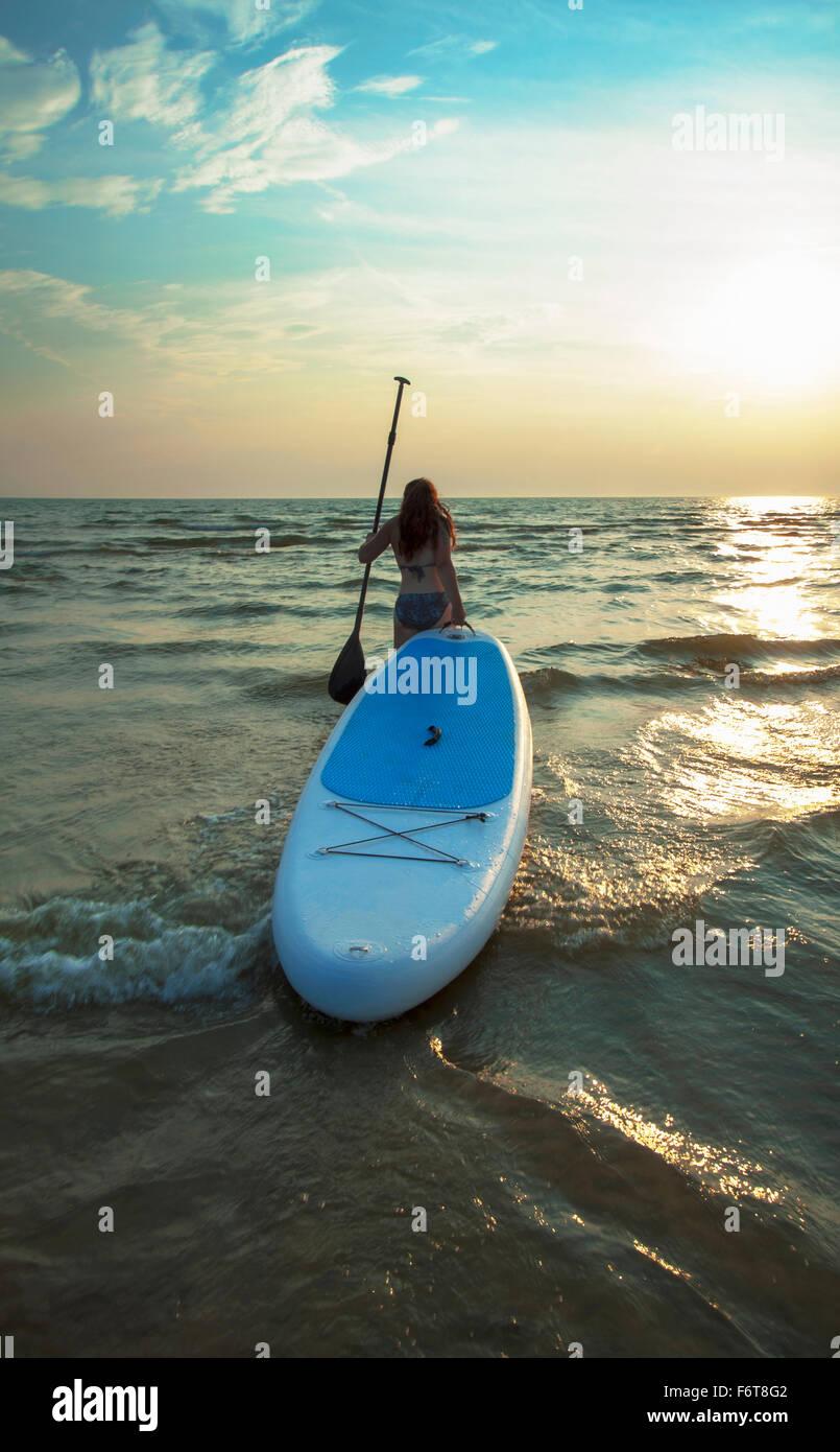 Donna tirando paddleboard nel lago Immagini Stock
