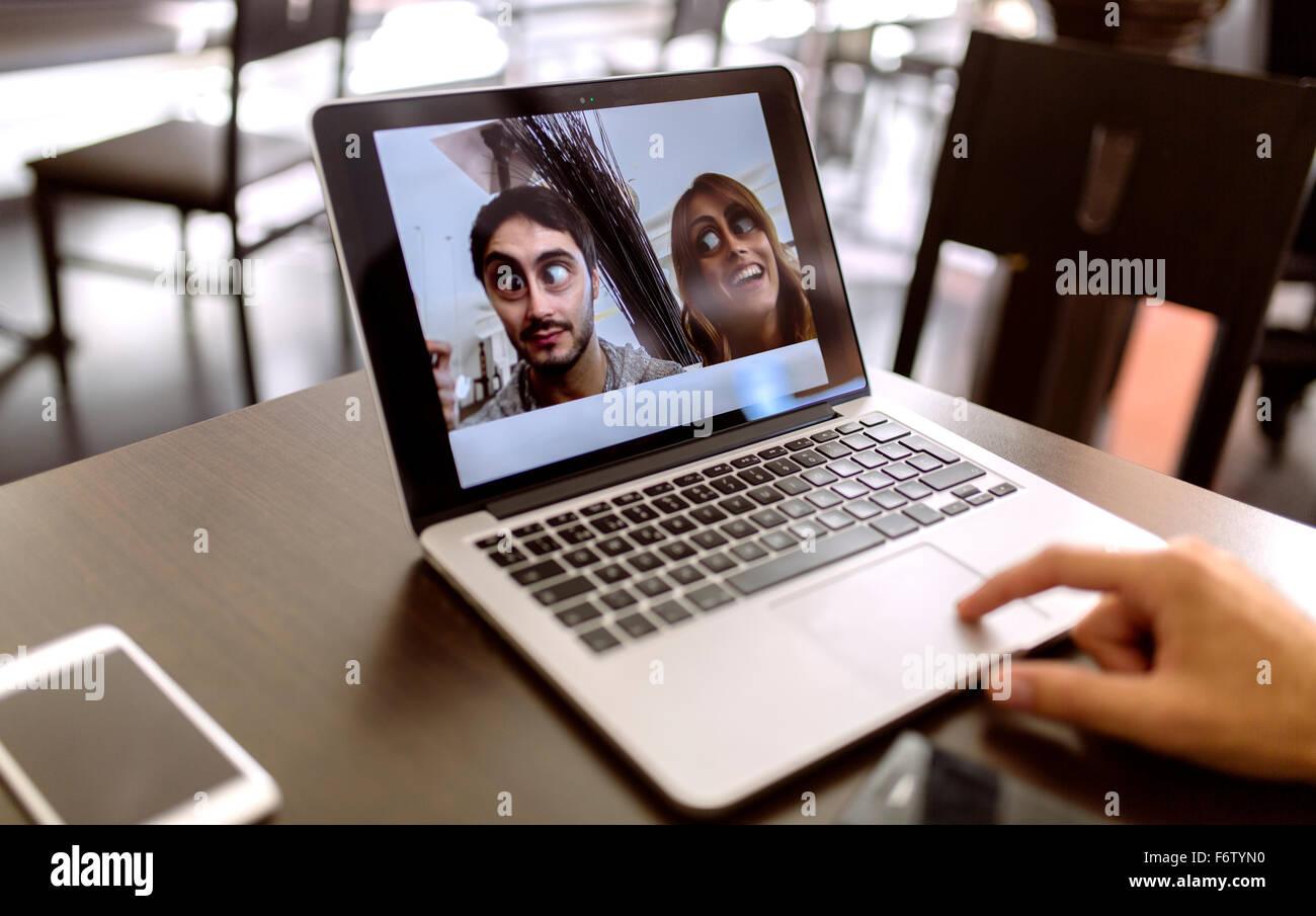 Divertente la fotografia di coppia giovane sul display del computer portatile Immagini Stock