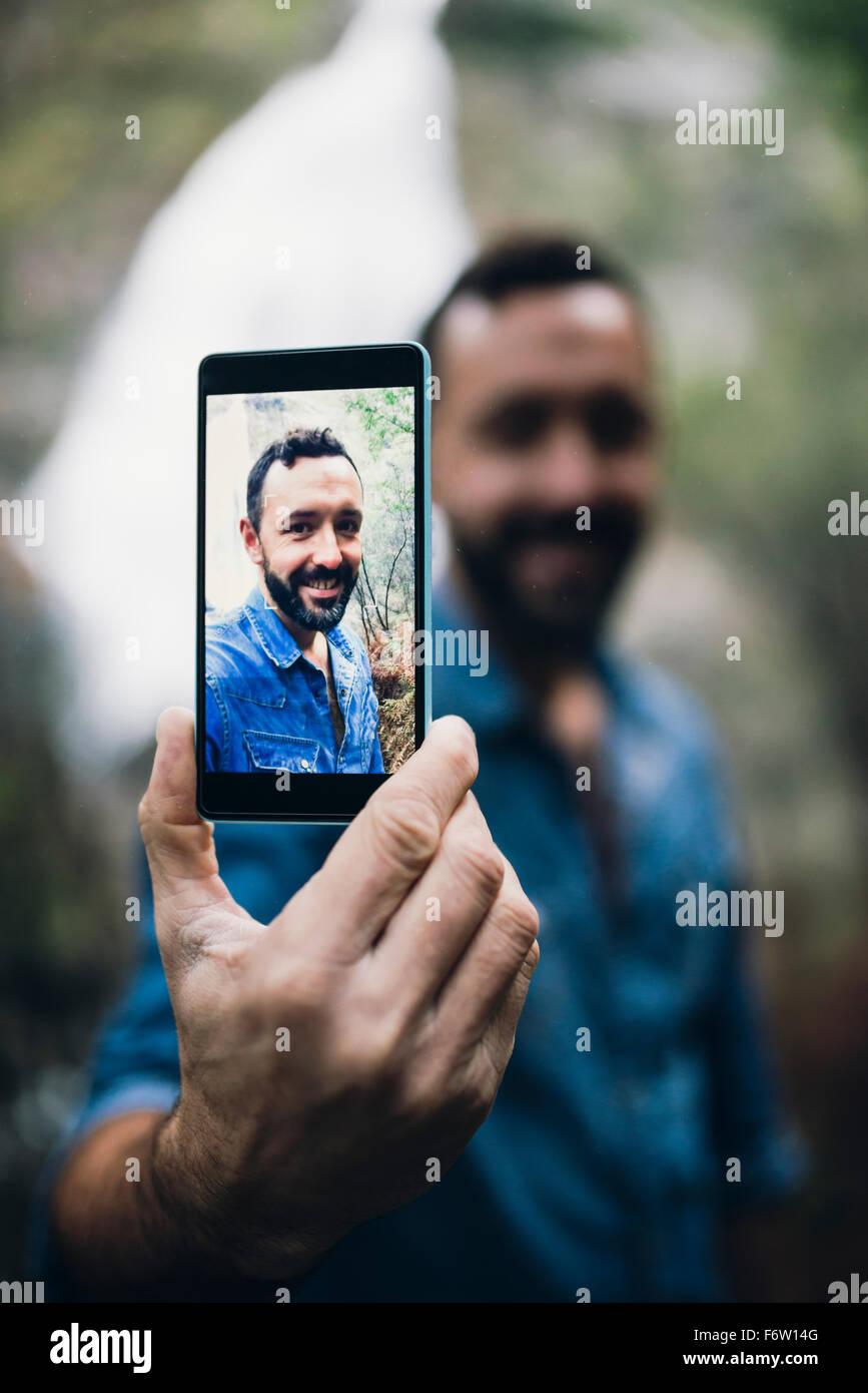 Uomo Barbuto che mostra selfie sul display del suo smartphone Immagini Stock