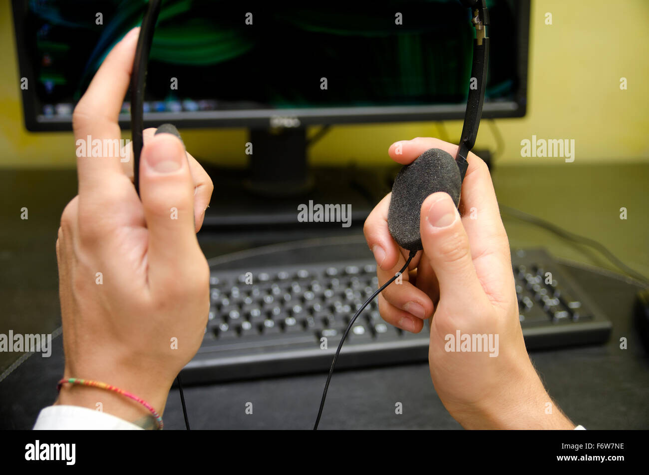 Il punto di vista di utente del computer mettendo sulle cuffie, alla sua scrivania. Auto prospettiva del giovane Immagini Stock