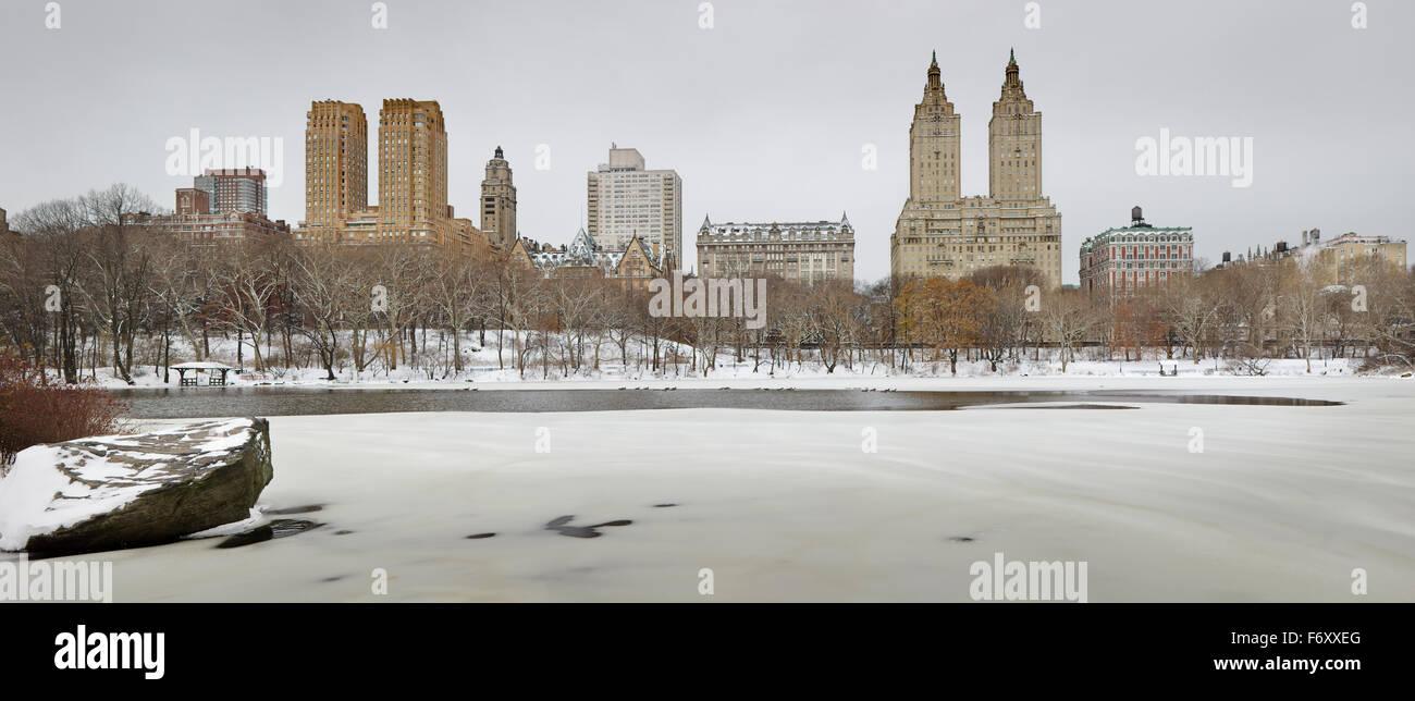 Inverno mattina dopo la nevicata nel Central Park e il lago ghiacciato. Manhattan Upper West edifici si ergono al Immagini Stock