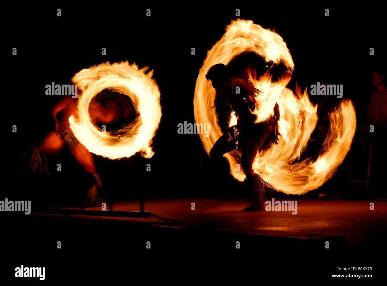 Coppia di concorrenti ballerini incendio filatura manganelli illuminata di notte dopo un luau Maui Hawaii Immagini Stock