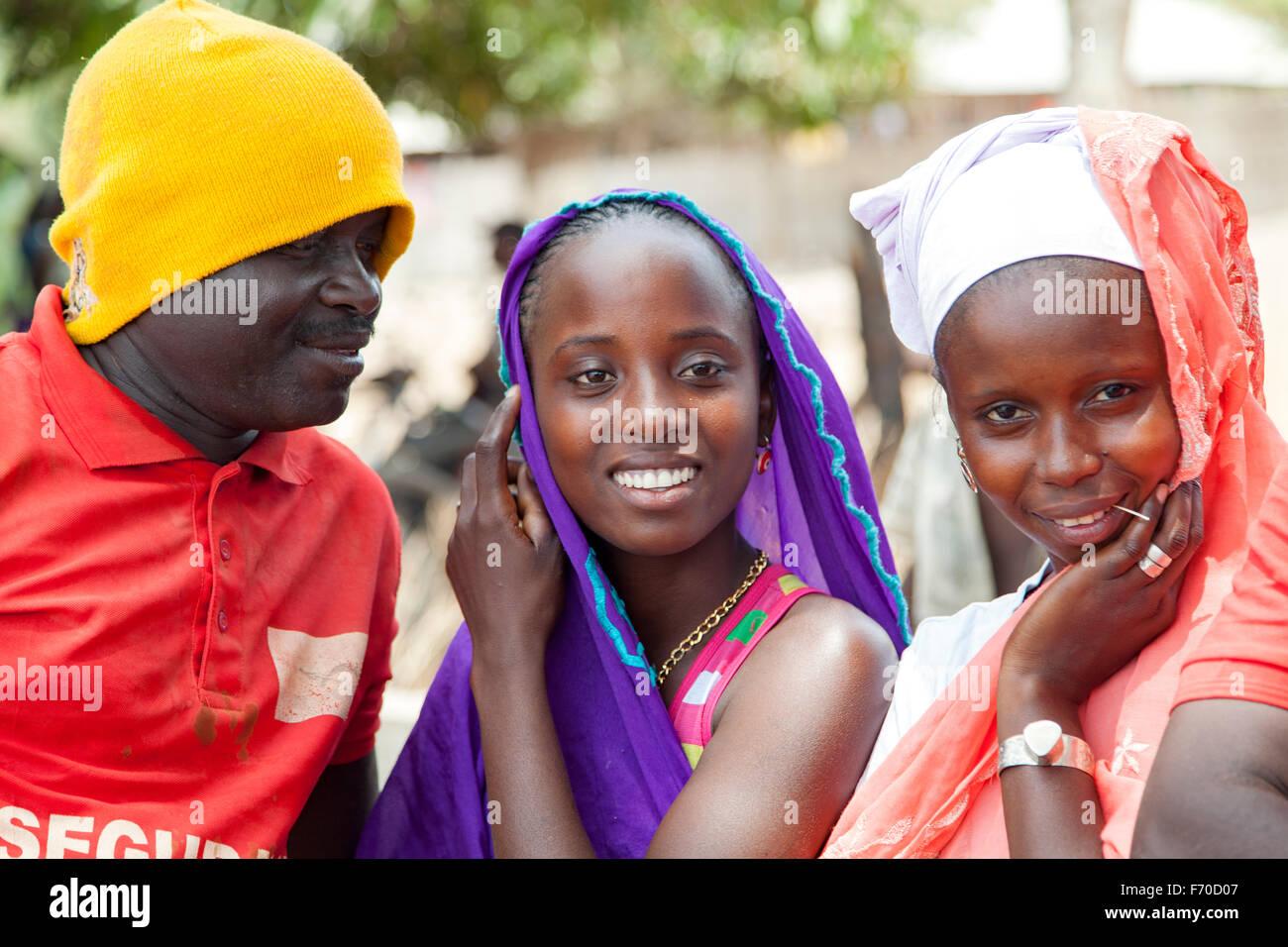 Gabu, GUINEA-BISSAU - 10 maggio 2014: uomo cercando di flirtare con due ragazze africane. daily scene rurali DALLA Immagini Stock