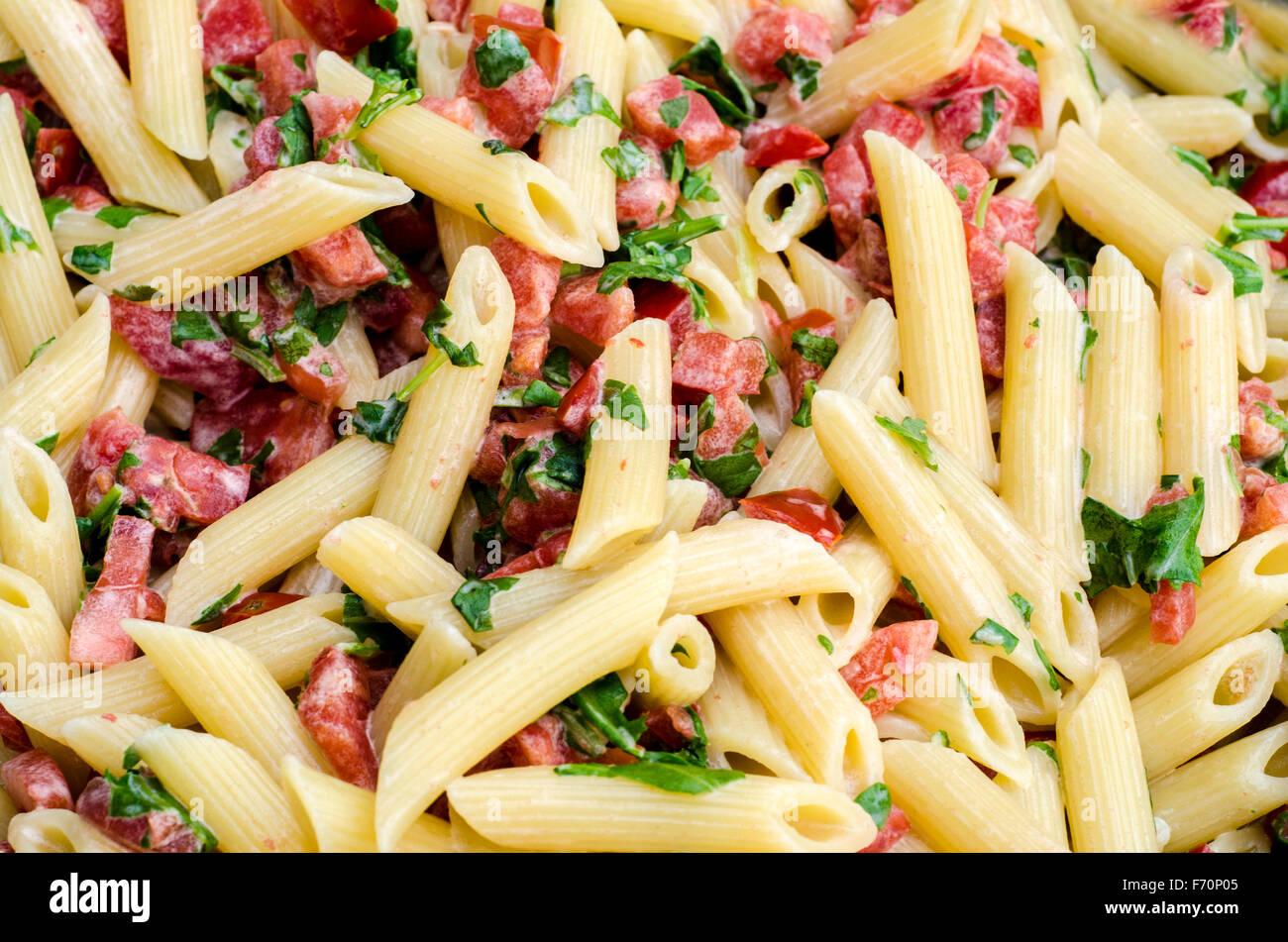 Il cibo italiano: Pasta chiamati mezze pennette con i pomodori in pezzi e foglie di rucola. Campione di texture Immagini Stock