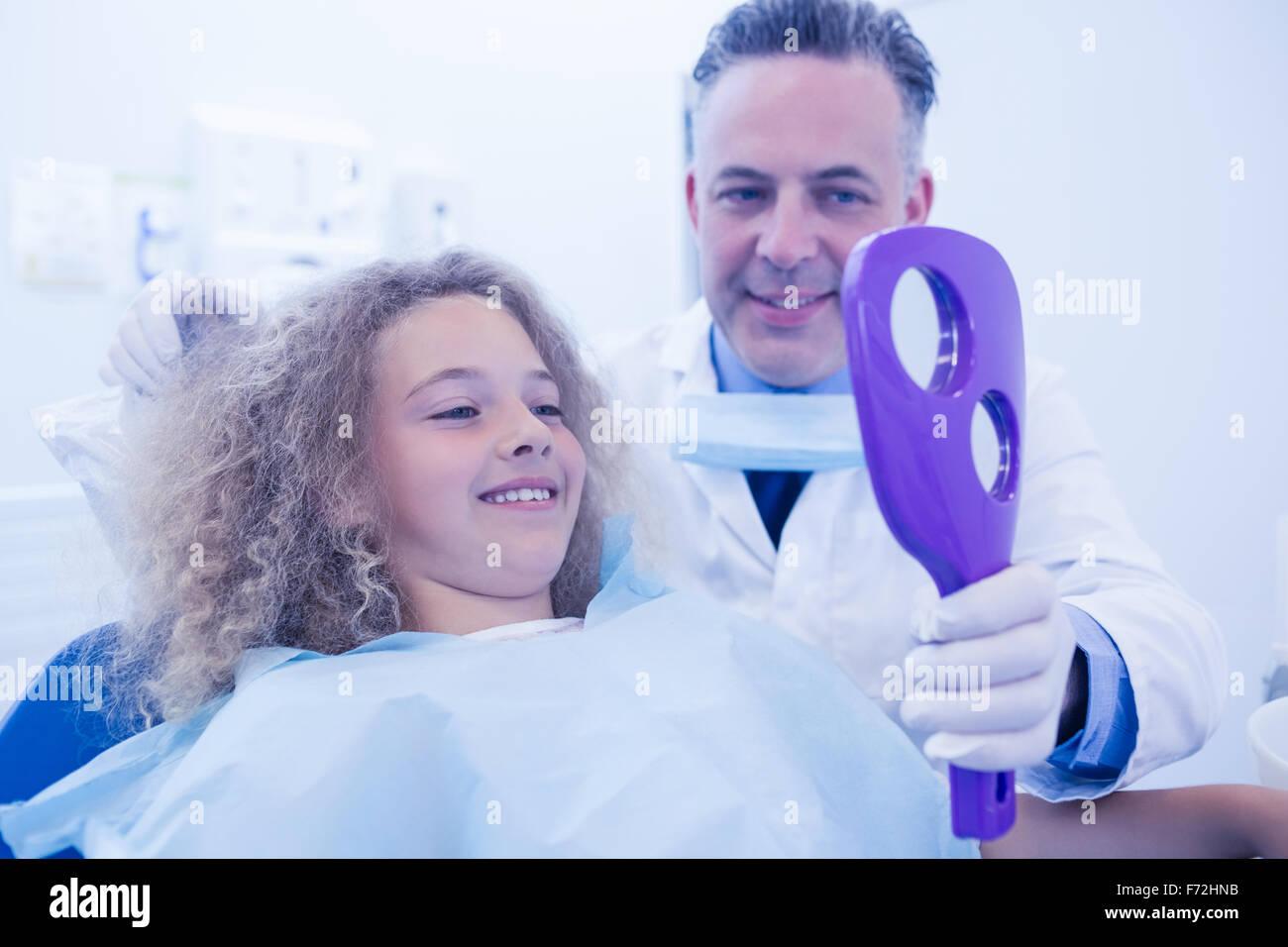 Dentista pediatrico che mostra il paziente nuovo sorriso Immagini Stock