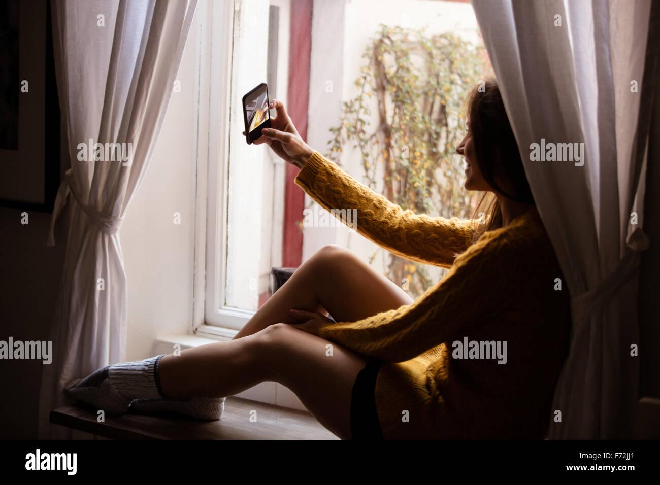 Giovane donna prendendo un selfie vicino alla finestra Foto Stock