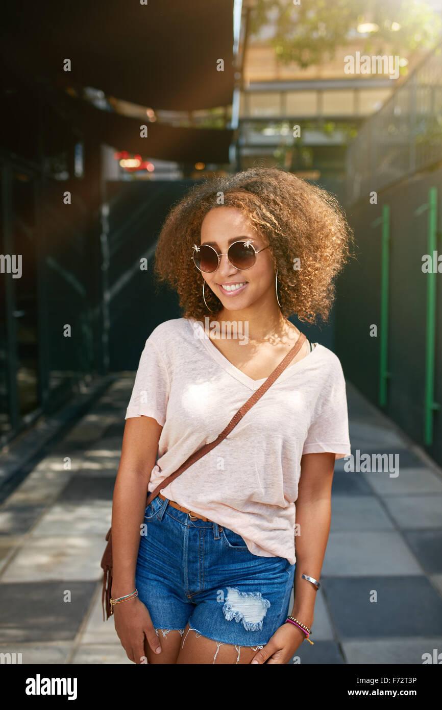 Ritratto di una giovane e bella donna nera indossando occhiali da sole sorride alla telecamera. I giovani africani in femmina casuals in posa all'aperto. Foto Stock