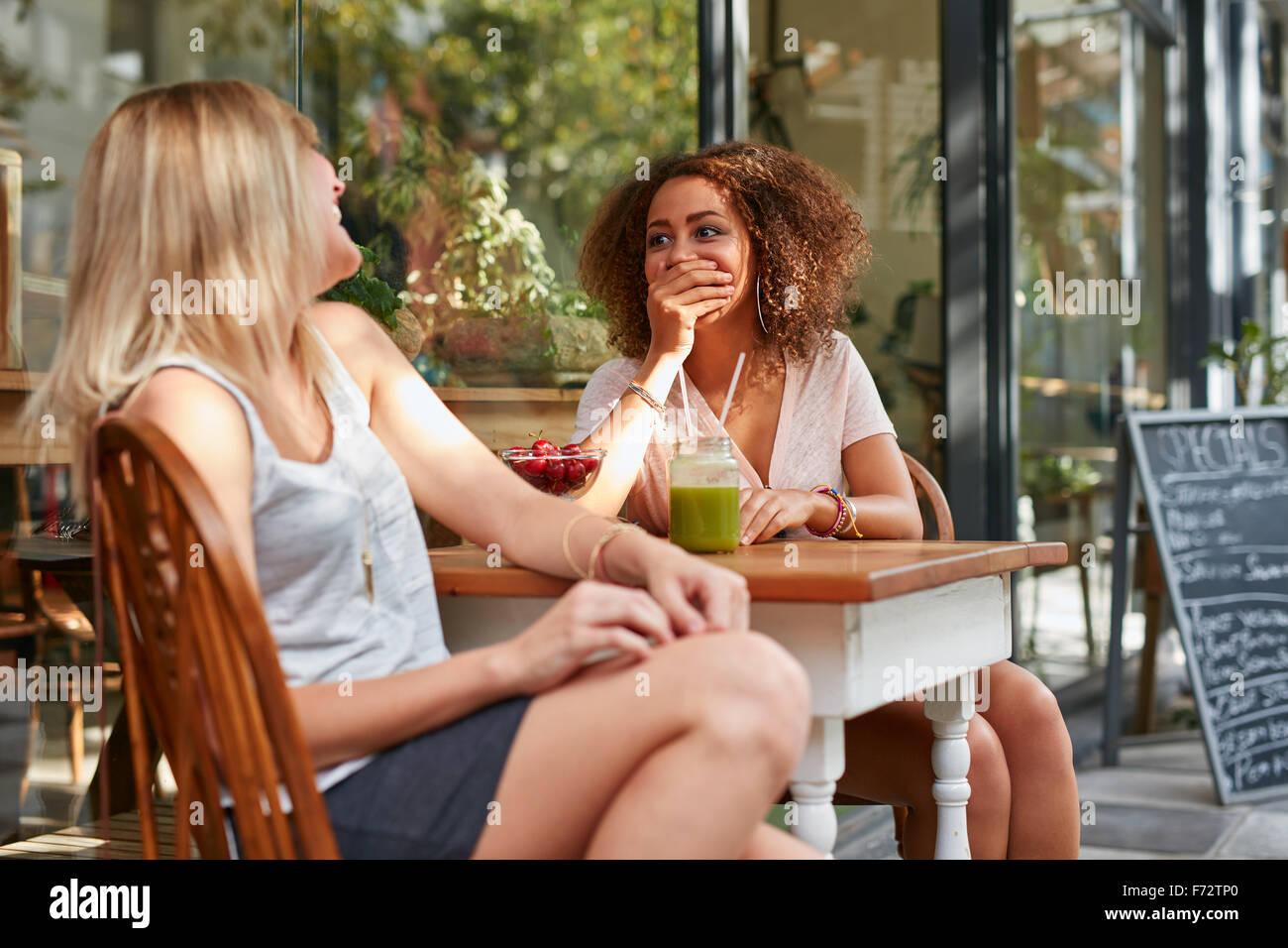 Due ragazze in chat e ridere mentre al cafè sul marciapiede. Amici di sesso femminile che condividono alcuni Immagini Stock