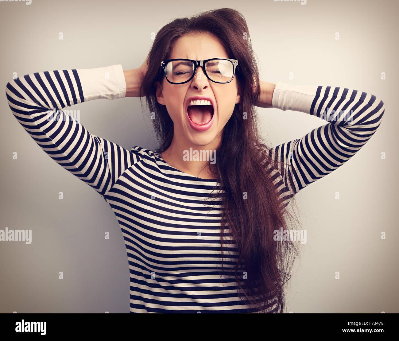 Angry Young business woman in bicchieri forte urlando selvaggio con bocca aperta e tenendo la testa con le mani. Immagini Stock