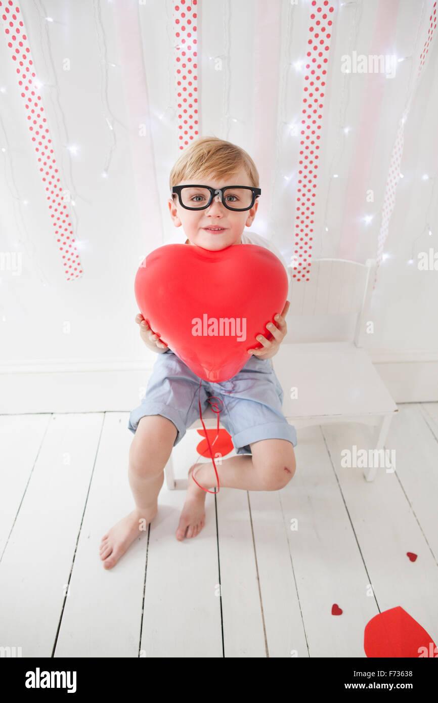 Ragazzo che posano per una foto in un studio di fotografi, tenendo palloncini rossi. Immagini Stock