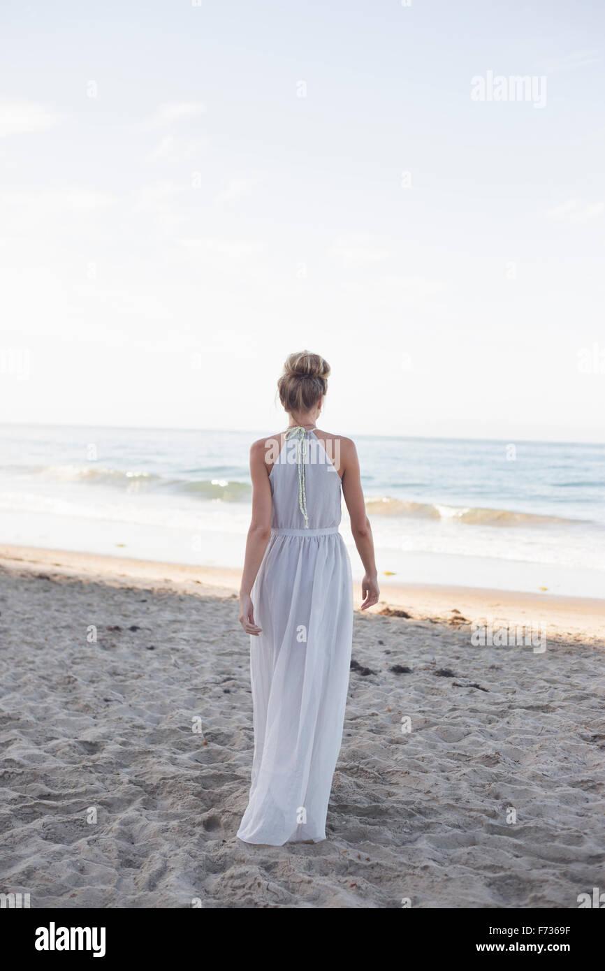 Donna bionda che indossa un abito lungo in piedi su una spiaggia di sabbia. Immagini Stock