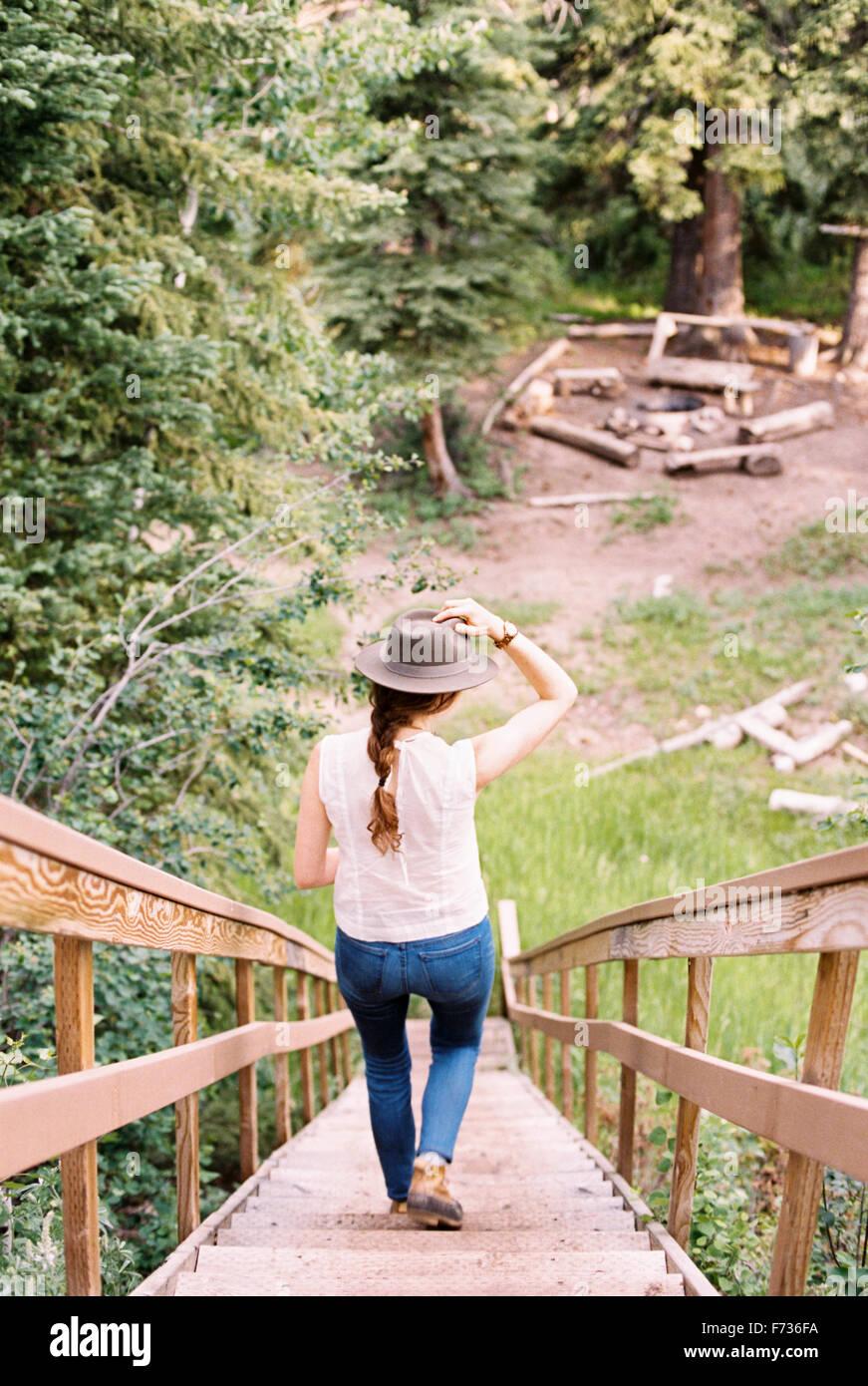 Angolo di alta vista di una donna che cammina verso il basso una ripida scala in legno. Immagini Stock