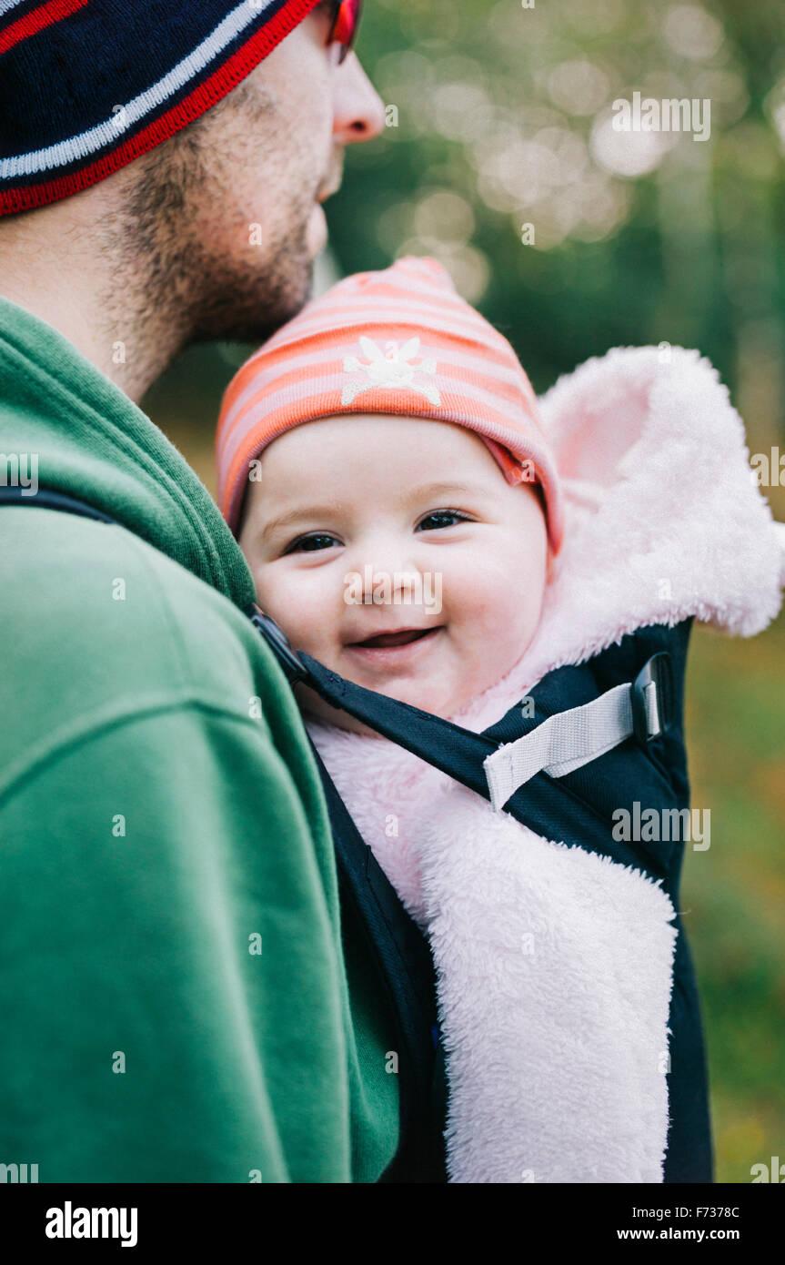 Un bambino in una imbracatura essendo portato da suo padre, all'aperto in inverno. Immagini Stock