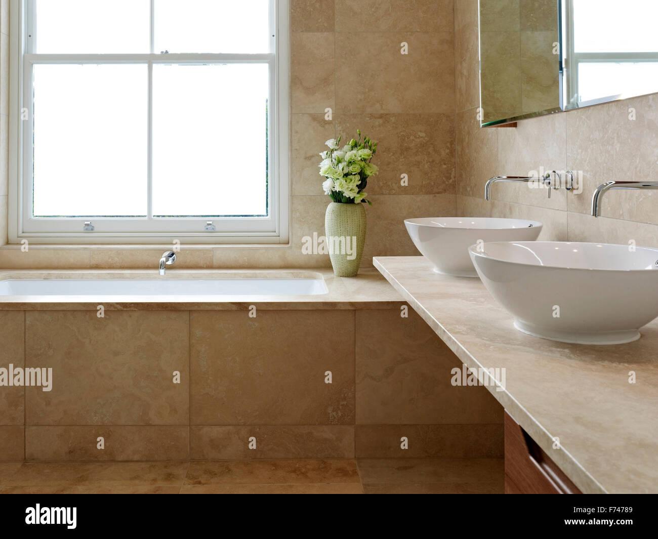 Doppi lavandini e vasca da bagno in vetro uncurtained in giardini
