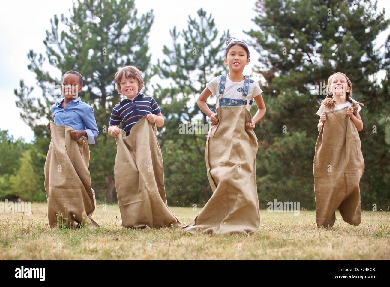 I bambini fanno concorrenza a sacco gara presso il parco Immagini Stock