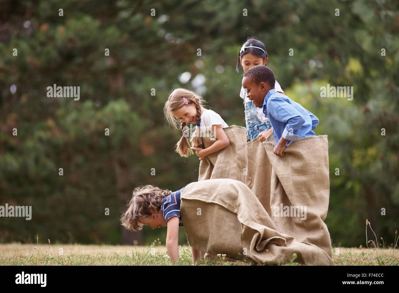 Gruppo di interracial kids concorrenti a sacco gara Immagini Stock