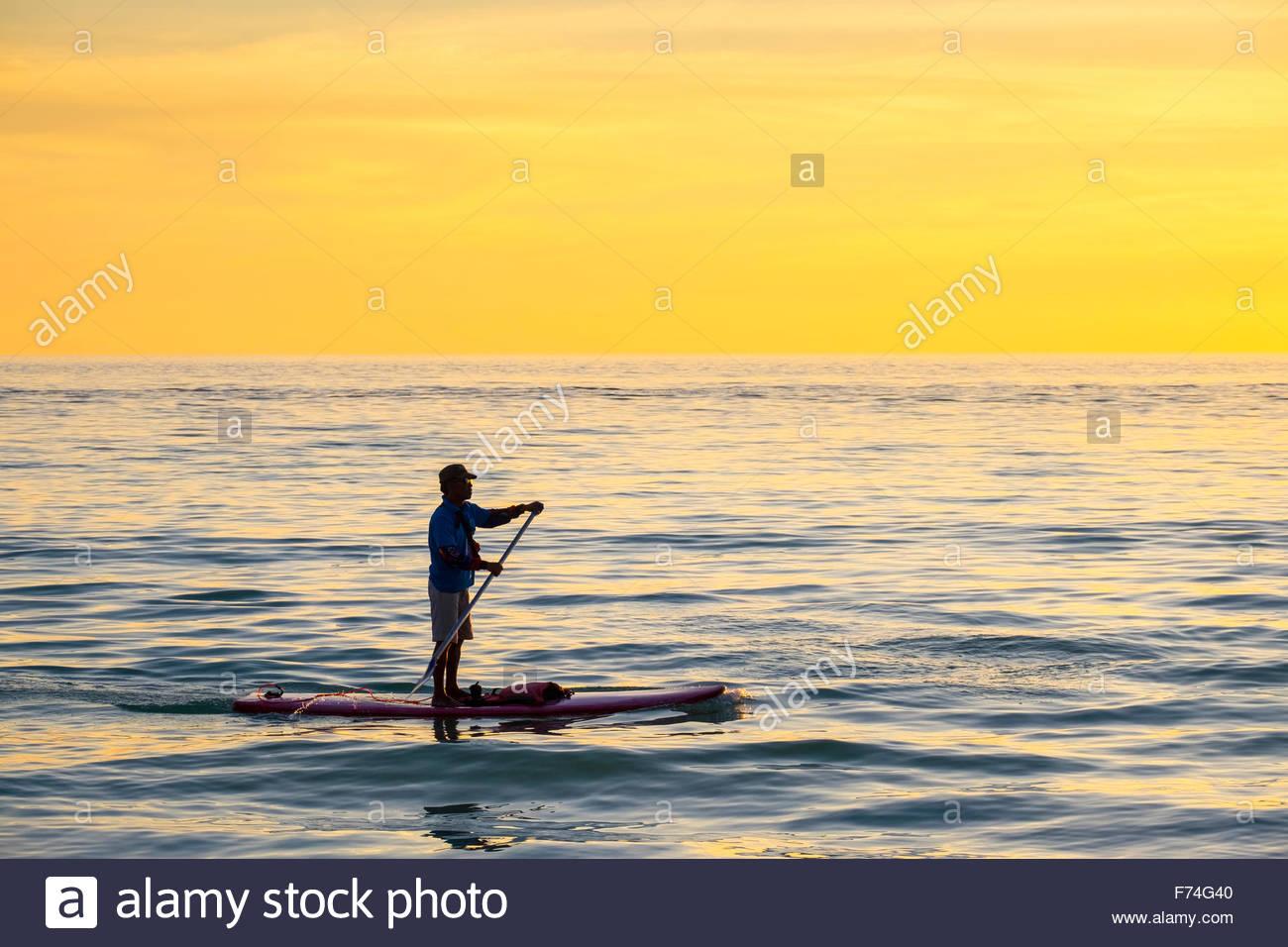 Un uomo su uno stand-up-paddleboard (SUP) al tramonto, Boracay Island, Aklan Provincia, Western Visayas, Filippine Immagini Stock