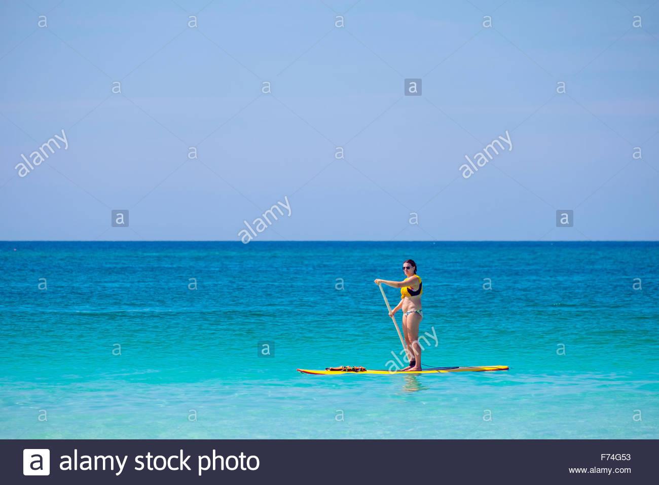 Donna in stand-up-paddleboard (SUP) in acqua blu, Boracay Island, Aklan Provincia, Western Visayas, Filippine Immagini Stock