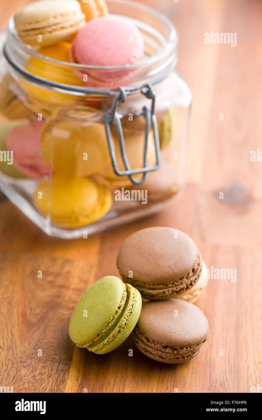 Gustosa macaron colorati in vaso sul tavolo di legno Immagini Stock
