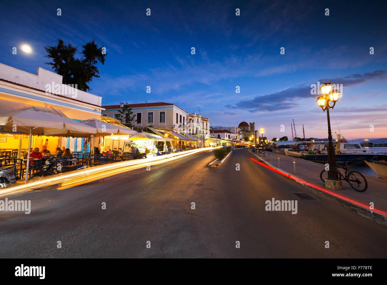 Vista del lungomare con i negozi di caffè, bar e ristoranti e barche da pesca nel porto di Aegina Island, Grecia Immagini Stock