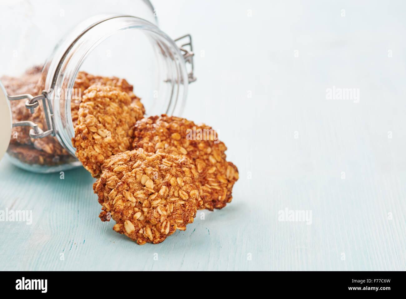 In casa i fiocchi d'avena banana cookies, jar e blu tavolo in legno Immagini Stock