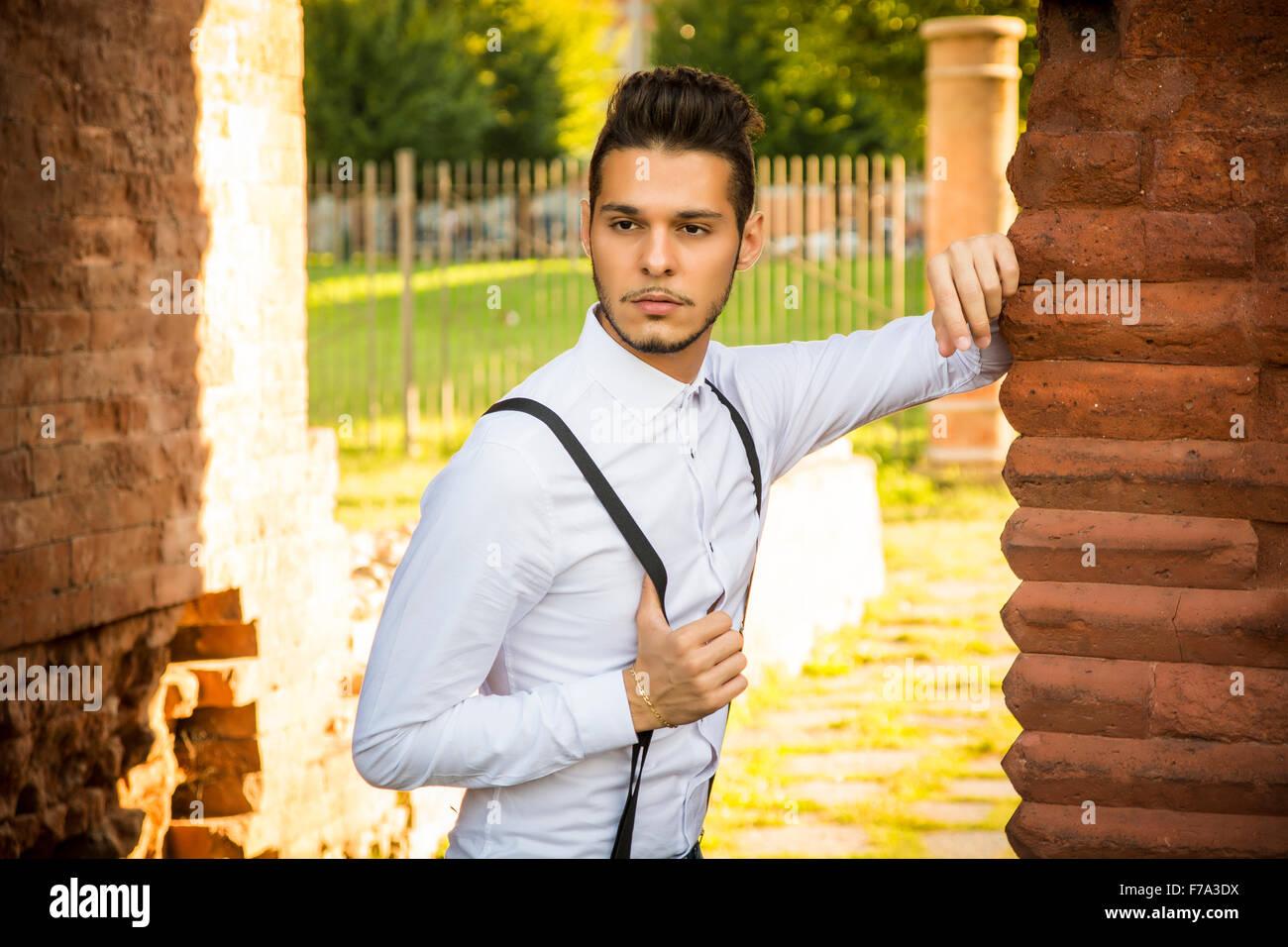 Attraente giovane uomo in piedi, appoggiata contro un muro di mattoni, guardando a un lato, grave. Tre quarti shot Immagini Stock