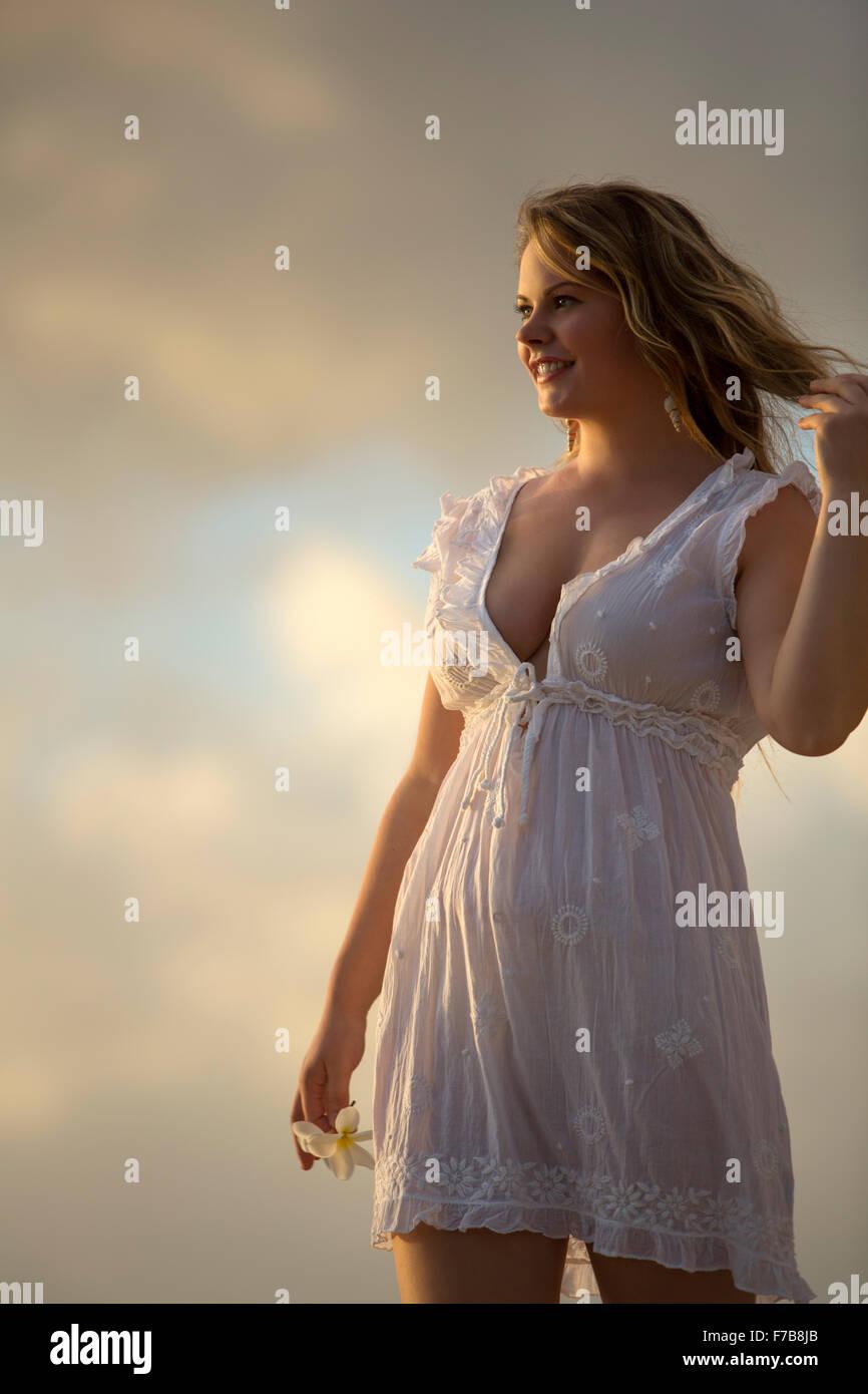 Giovane femmina adulta in sun condire con la plumeria sbocciare nella mano destra, sorridente con i capelli nella Immagini Stock