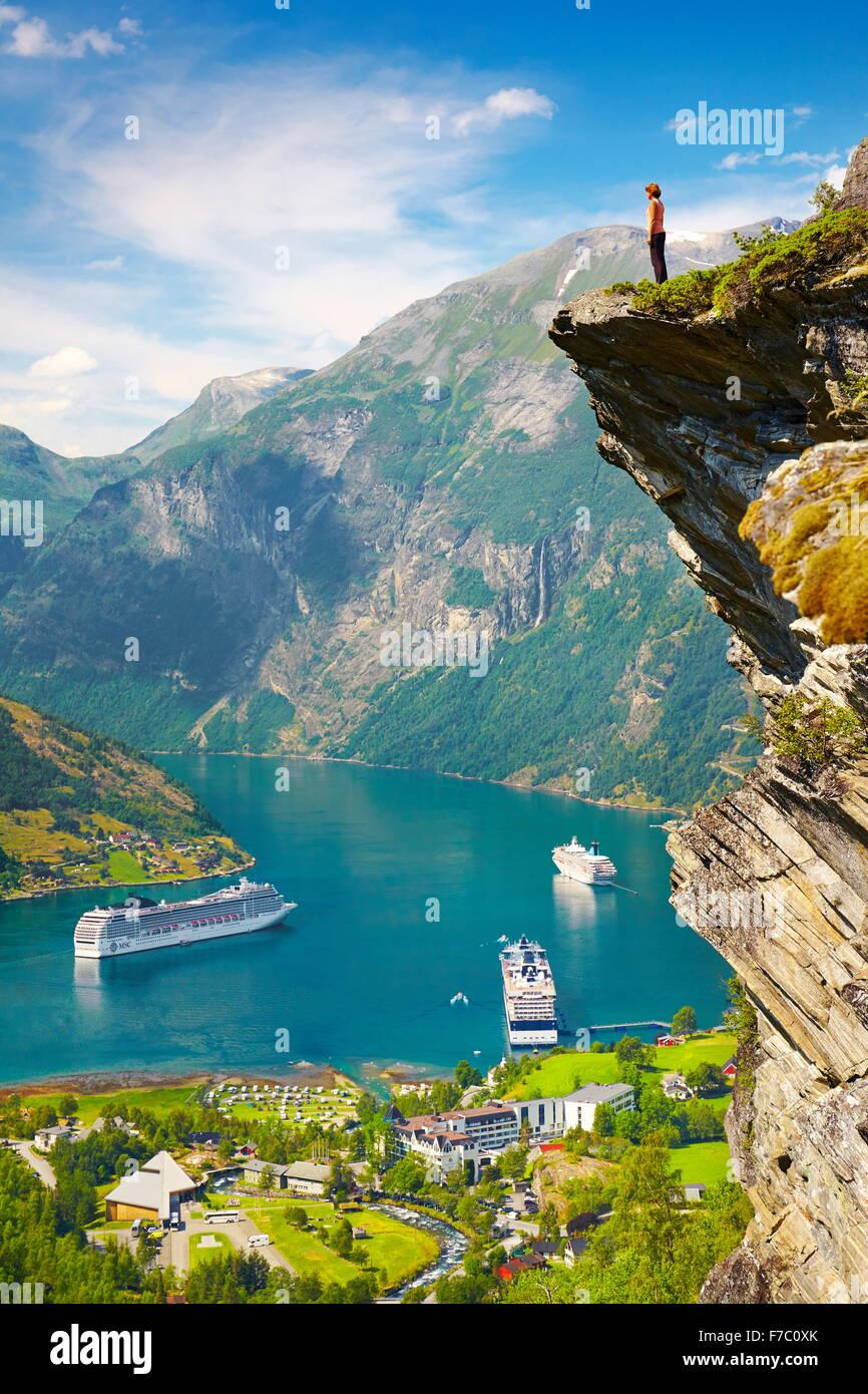 Tourist permanente sulla roccia, navi da crociera in background, Geiranger Fjord, Norvegia Immagini Stock