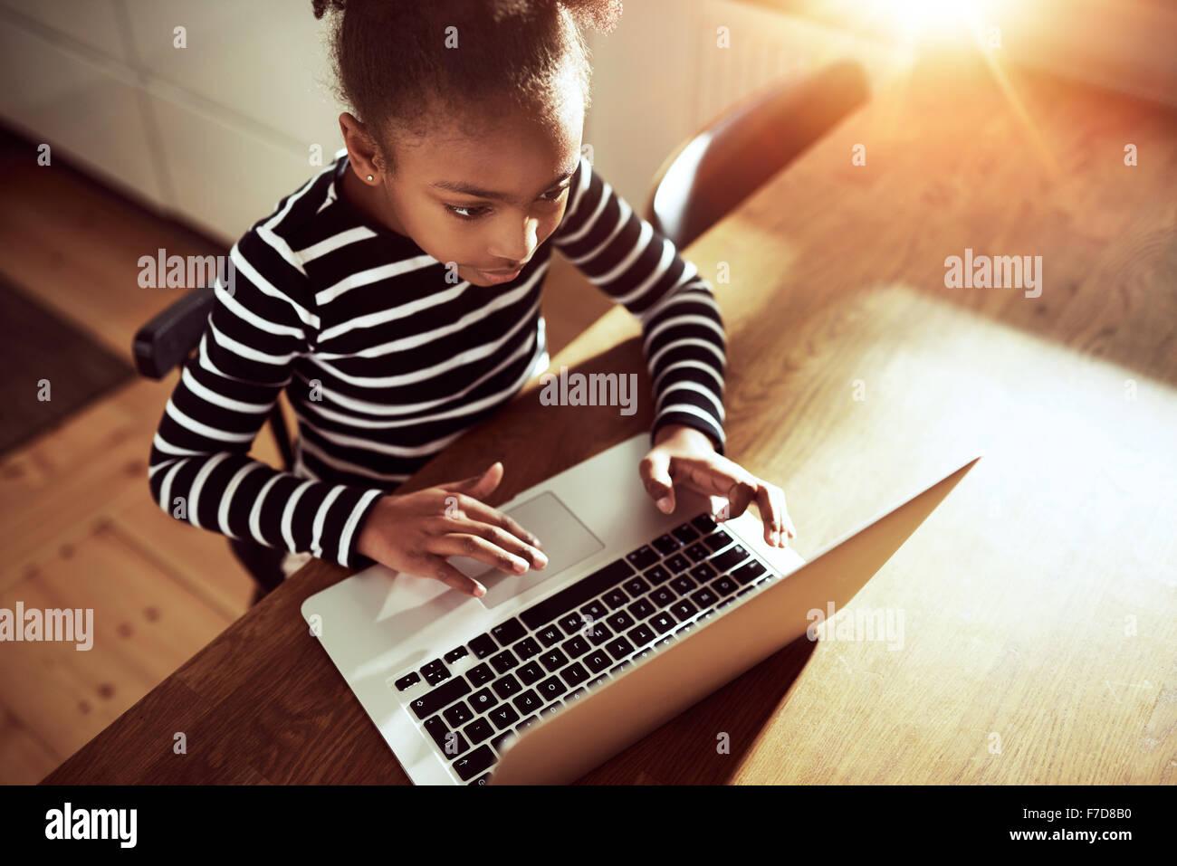 Angolo di alta vista da sopra di un simpatico giovane ragazza africana per navigare sul web in un computer portatile Immagini Stock